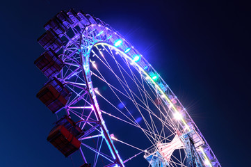 Ferris wheel with multi-colored illumination against night sky
