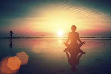 Girl sitting on the beach during sunset and meditating in yoga pose. Runner girl in the background.