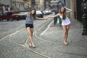 Two girls girlfriends walk along the tram tracks and fooling around in old town.