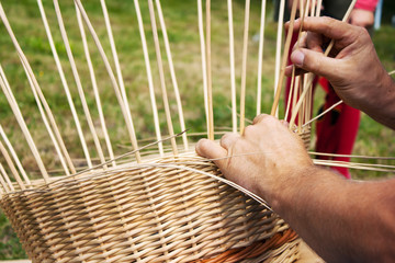 male hands braiding wicker basket