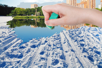 hand deletes winter snow field by rubber eraser