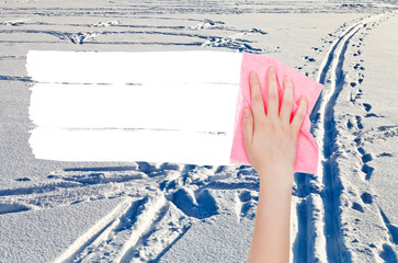 hand deletes winter snow field by pink rag