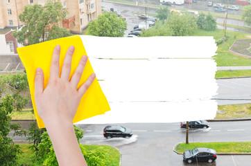 hand deletes rain on street by yellow rag