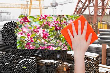 hand deletes industrial landscape by orange cloth
