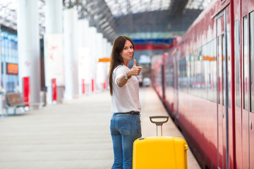 Young caucasian woman with luggage at station traveling by train