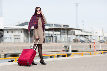 Young woman carrying luggage.