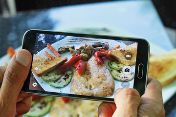 Male hands with smartphone taking photo of grilled chicken with