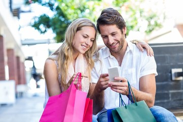 Smiling couple with shopping bags sitting and using smartphone