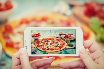 Woman taking a photo of Pizza and Ingredients with smartphone