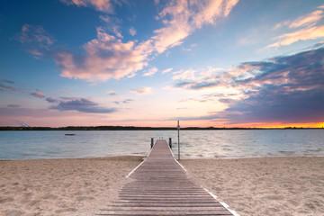 Fototapeta langer Holzweg zum See obraz