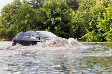 Car trying to drive against flood on the street in Gdansk, Poland