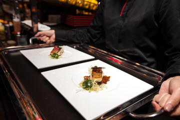 chef put food on tray before served by waiter