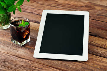 White tablet computer with a glass glass of cola with ice and mi