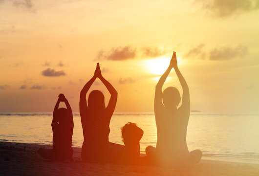 family silhouettes doing yoga at sunset
