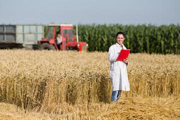 Woman agronomist in wheat field Wall mural