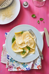 Italian Ravioli Served with Basil and Parmesan Cheese, Rose Painted Table on Background