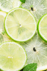 Sliced lemon, lime and mint leaves on a dark background, top vie