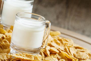 Milk in a cup and corn flakes, selective focus