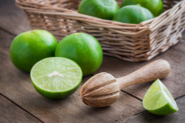 Wooden squeezer and lime on table
