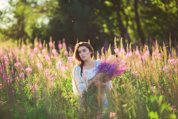 Beautiful young girl, holding lavender in a field on sunset. wal