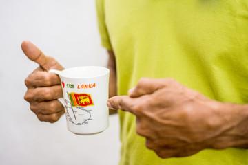 A man pointing to Sri Lankan flag printed on a mug