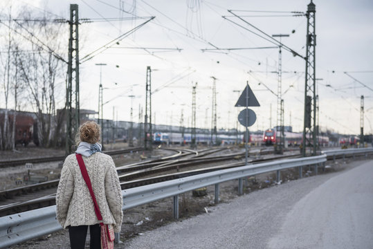 Rear view of a young woman curiously looking at train on railway track, Munich, Bavaria, Germany