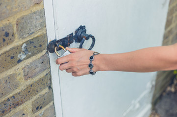 Female hand touching padlock outside