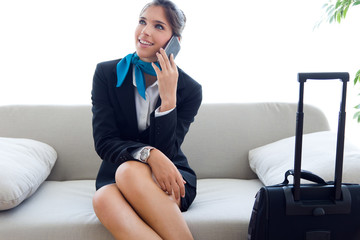Beautiful hostess in airport with mobile phone.