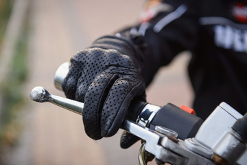 protective biker gloves on a motorcycle wheel
