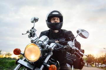 Biker in helmet driving motorcycle on sunset.
