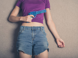 Young woman with water pistol on carpet
