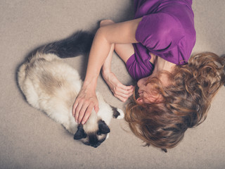 Woman with cat on carpet