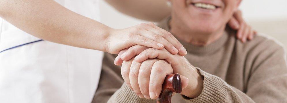 Senior man and caring nurse