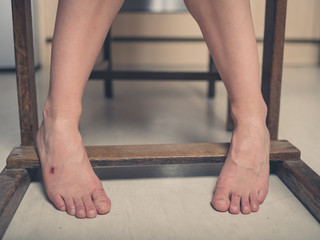 Feet of young woman with a scab