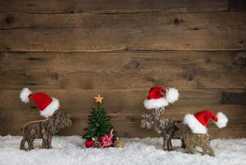 Weihnachten Dekoration aus Holz mit Rentiera und Santa Claus Mützen in rot weiß mit Tannenbaum.