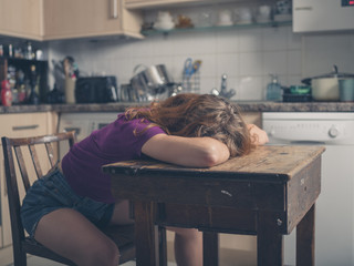 Woman resting at table in kitchen