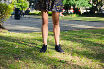 Legs of young woman standing on grass in park