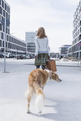 Rear view of woman walking on road with dog and suitcase, Munich, Bavaria, Germany