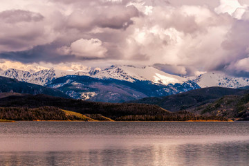 A lake leading to storm clouds over a snow-capped mountain.