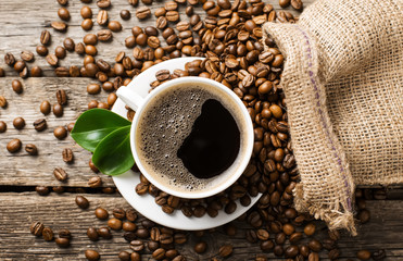 ground coffee in scoop and coffee beans on a wooden background,