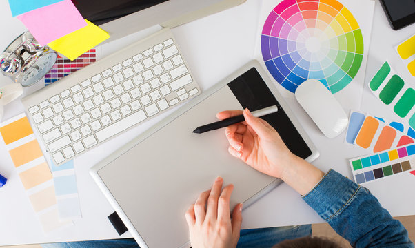 Young pretty Graphic designer using graphics tablet to do her wo