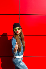 Close up fashion lifestyle portrait young hipster girl, wearing bright make up and yellow sunglasses, making sexy faces. Urban red  wall background.
