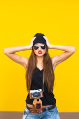 Close up fashion lifestyle portrait young hipster girl, wearing bright make up and  sunglasses, making sexy faces. Urban yellow  wall background.