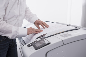 Man using photocopier in office, Munich, Bavaria, Germany