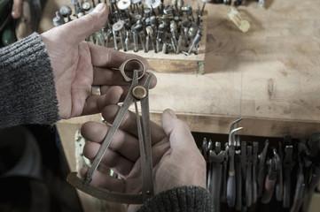 Senior male goldsmith measuring a metal ring, Bavaria, Germany