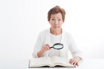 虫眼鏡を使って本を読んでいる高齢者の女性