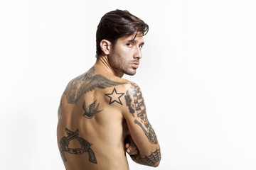Sexy tattooed man back portrait looking at camera
