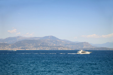 Seascape with mountains at the background and white yacht sailing in sea waters
