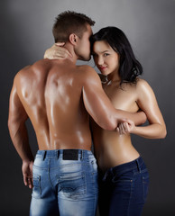 Flirtatious woman and strong man posing in studio