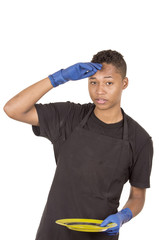 Hispanic young man wearing blue cleaning gloves holding green